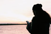 a woman looking at her cellphone standing in front of a calm sea at sunset