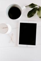 iPad, coffee mug, candle, matches, white table
