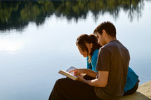 Couple reading the Bible while sitting on a pier at a lake.