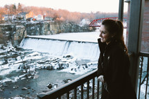 a woman looking out at a snowy river and waterfall
