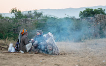 men sitting by a fire in India