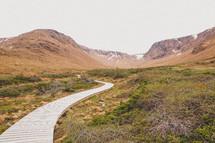 a wood boardwalk path through a mountain valley