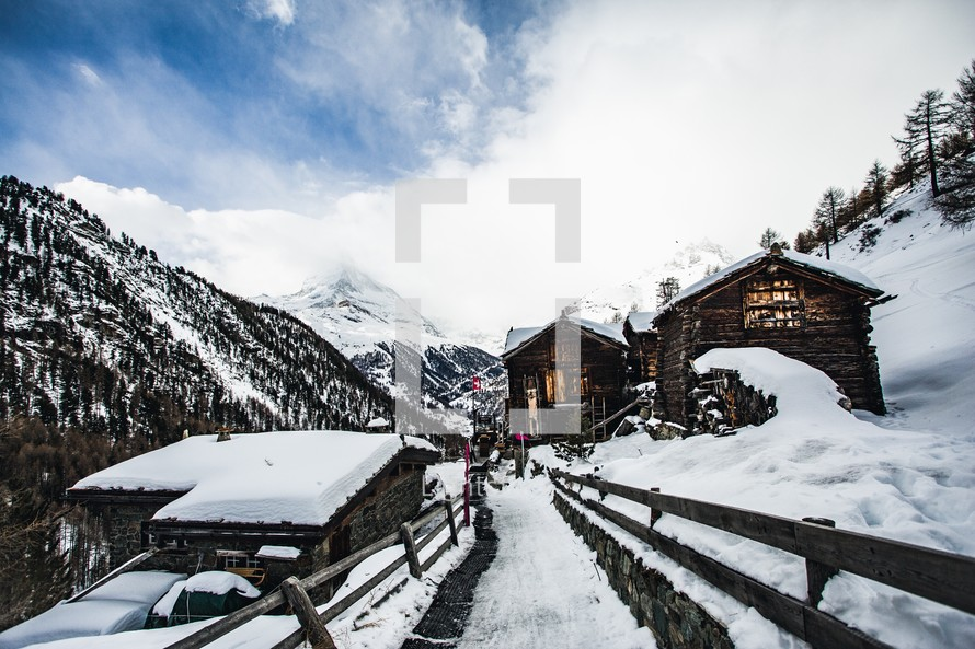 A small snow covered village with wooden cabins near Zermatt, Switzerland with the Matterhorn covered in clouds