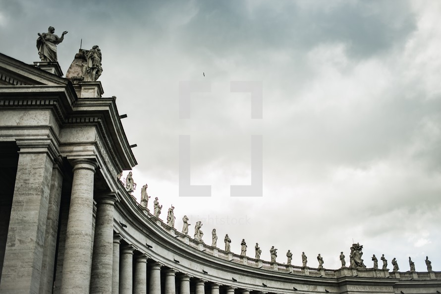 Curved view of ancient statues on top of pillars in the courtyard of St. Peter's Basilica at the Vatican in Rome
