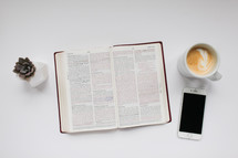 succulent plant, open Bible, phone, and latte