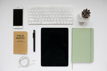 iPhone, computer keyboard, iPad, field notes book, pen, journal, succulent plant, earbuds, white background, desk, workspace, electronics