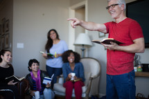 A man leading a Bible study for a small group of people.