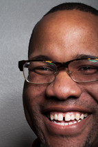 The face of a smiling man wearing glasses.