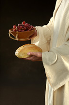 Jesus' hands holding a loaf of bread and a bowl of grapes.