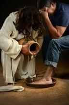 Jesus washing the feet of a man.