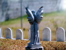 A Guardian angel statue stands guard over a group of children's graves in a cemetary. It is a humbling sight for a parent to have to bury their children but even in death there is victory as the scripture says in 1 Corinthians 15:55- - O death, where is thy sting? O grave, where is thy victory?