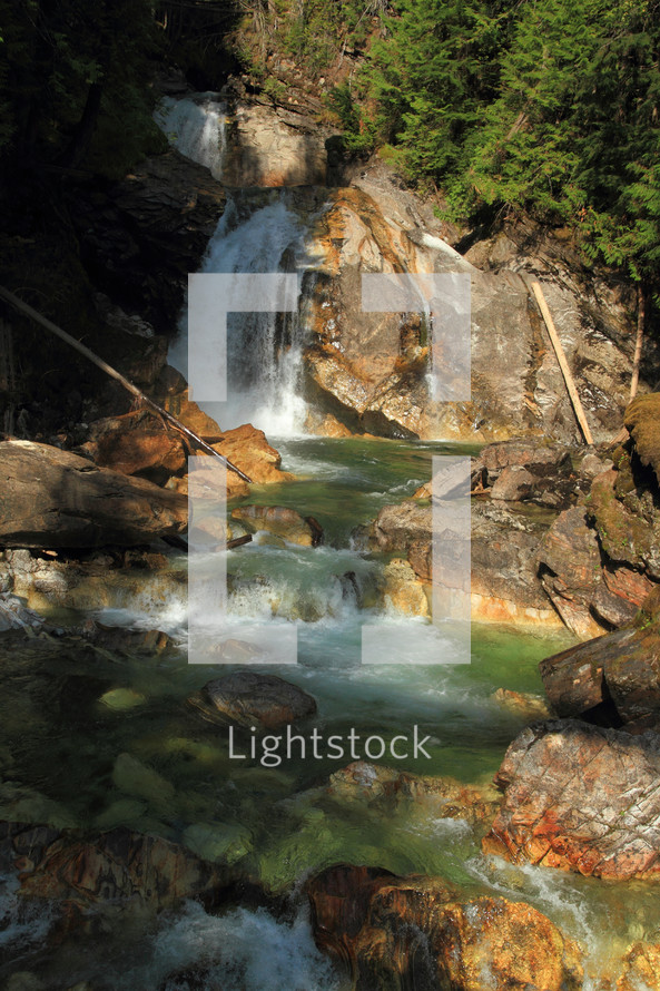tumbling waterfall flowing into a rocky stream