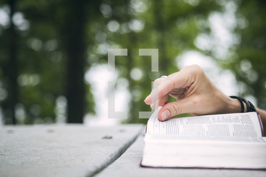A hand turning a page of the Bible.