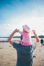 infant girl on her father's shoulders at the beach