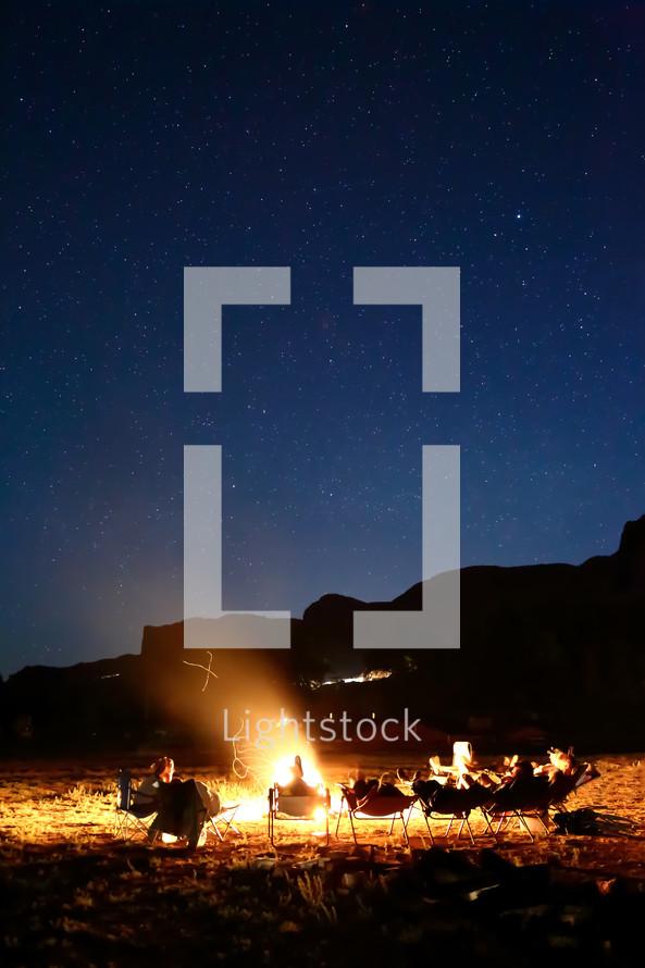 sitting around a campfire under starlight