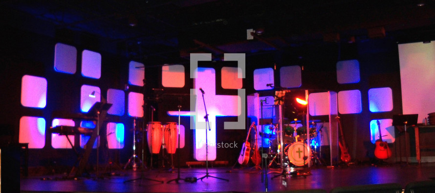 A lighted sound stage for recording music, playing concerts or having a live worship band. The stage is decorated with a cross, lighting, lighted panels and musical instruments including guitars, drums, microphones, bass guitar and other instruments for leading a live praise and worship church service.