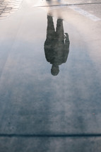 silhouette reflection of a man in a puddle