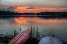 Kayaks on lake shore at sunset.