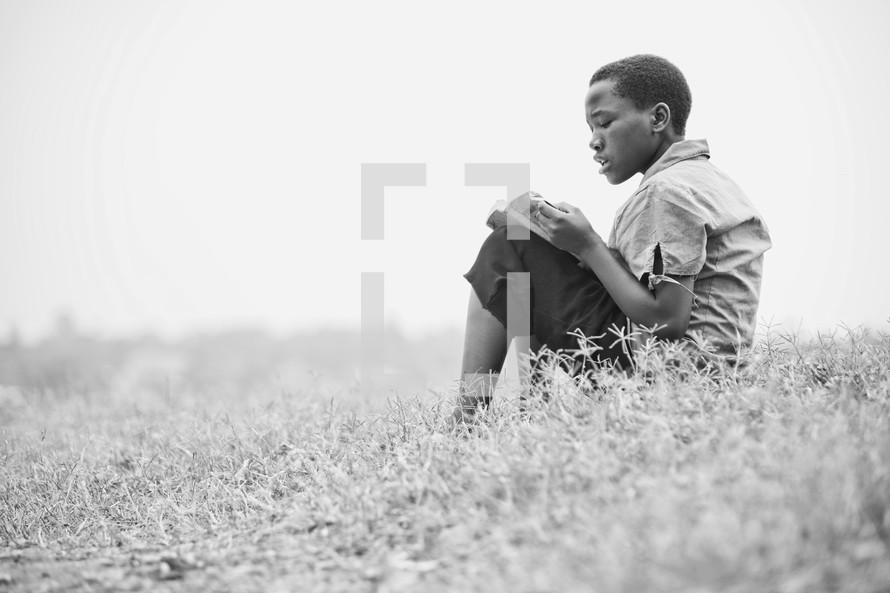 Boy reading bible in field