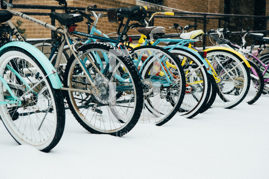 bicycles parked on a bike rack in the snow