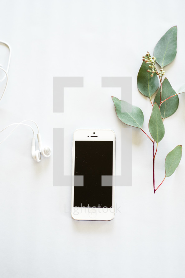 Earphones, a cell phone, and a sprig of green leaves on a white background.