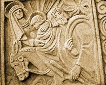 A stone carving of Jesus, Mary and Joseph on a donkey. The artwork is representative of a Mayan or Aztec Indian carved relief depicting a young Jesus travelling with his mother and father through Jerusalem.