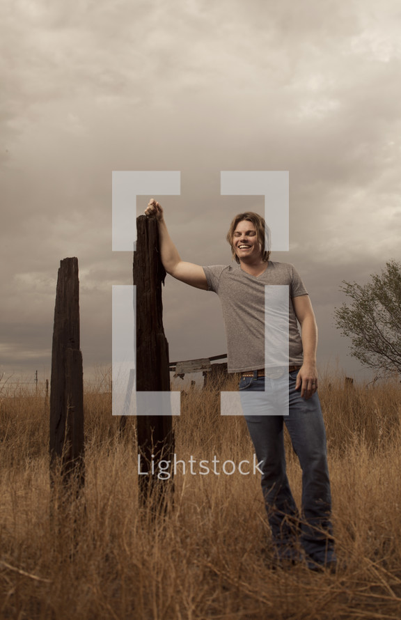 man leaning against an old fence post