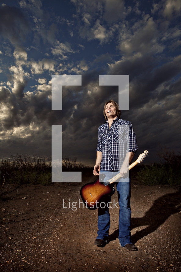 man holding a guitar by the neck under a cloudy sky