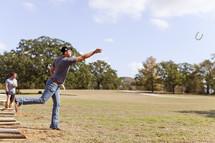 man throwing horseshoes