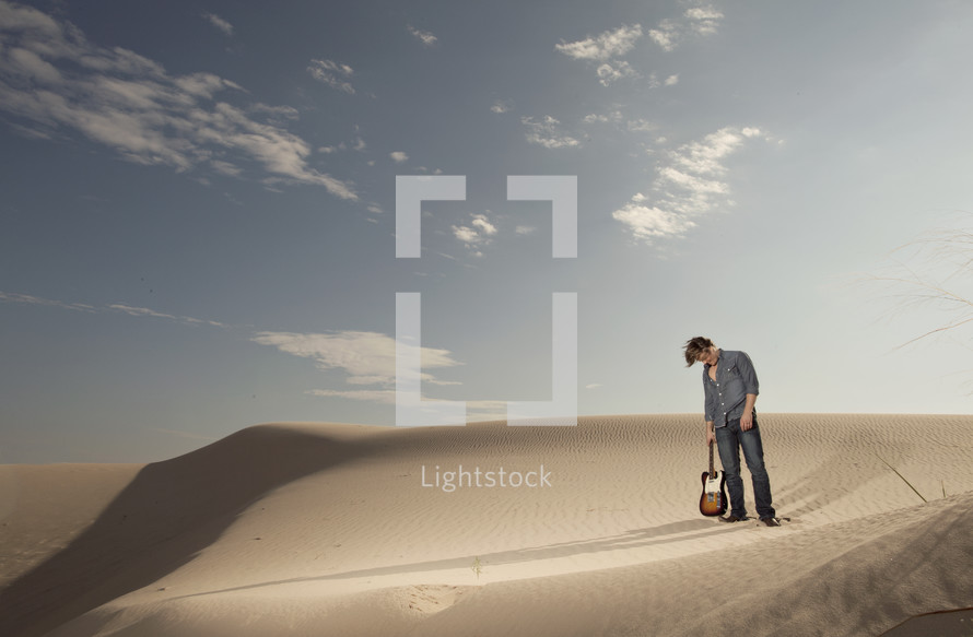 man holding a guitar by the neck standing on sand dunes