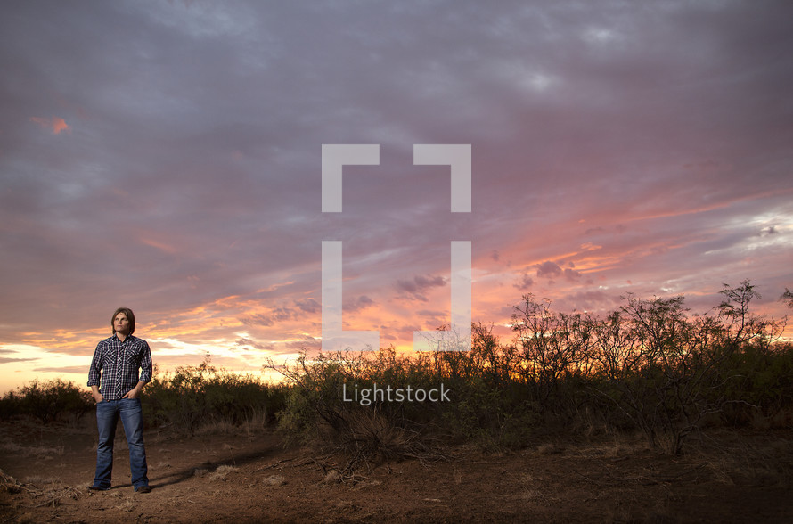 man standing under a colorful sky at sunset