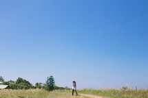 Couple hugging while standing on a dirt road in a grassy field.