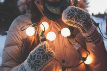 A woman in coat and mittens holds a string of lights.