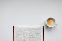 open Bible and mug on a white background