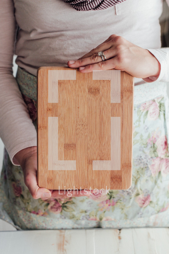 a woman holding up a cutting board