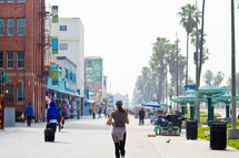 Pedestrians in the sidewalk along a beach front shopping center in Los Angeles.