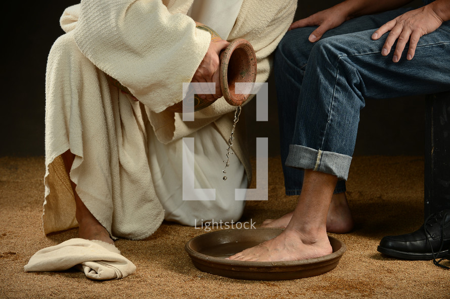 Jesus pouring water from a jug to wash feet.