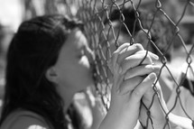 couple kissing through a chain linked fence