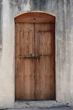 Vintage wooden door in a stucco building.
