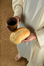 Jesus' hands holding a loaf of bread and a cup of wine.