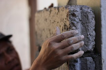 a man setting a brick in mortar