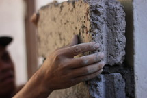 a man setting bricks in mortar