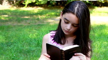 Young girl reading Holy Bible. Spiritual moment for a teenage girl.
