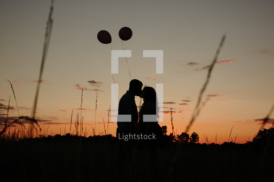 Couple kissing at sunset near floating balloons