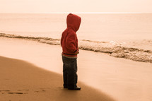 toddler boy standing on a shore