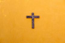wood cross on a yellow wall