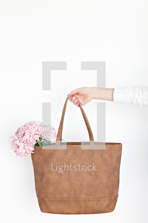 a woman carrying pink flowers in her purse