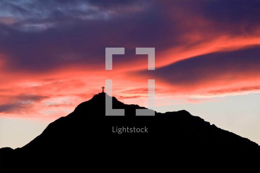 cross on a mountain peak at sunset