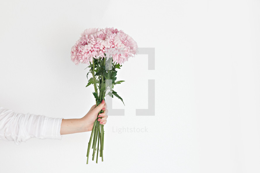 a woman holding a bouquet of pink flowers
