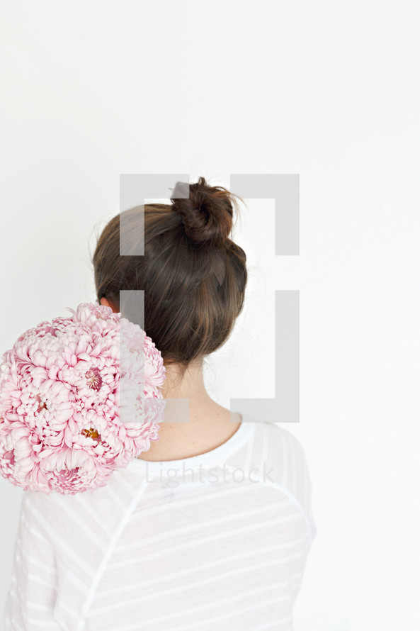 a woman holding a bouquet of flowers over her back